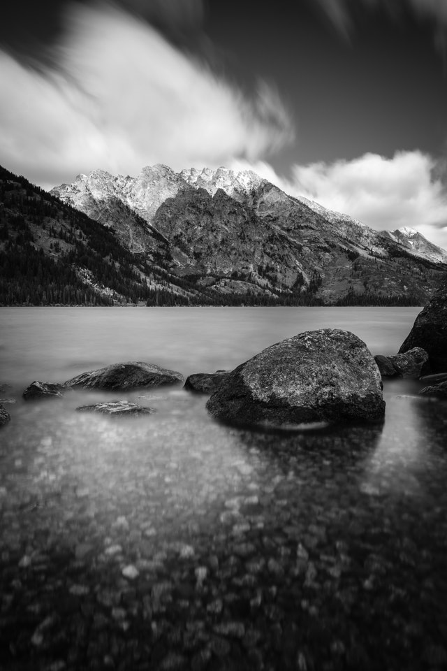 A long exposure of the shores of Jenny Lake in Grand Teton National Park. In the background, Mount Saint John.