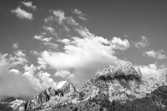 Symmetry Spire and Rockchuck Peak seen under morning clouds from String Lake.