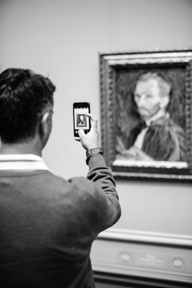 A person taking a photo of a self-portrait of Vincent van Gogh at the National Gallery of Art.