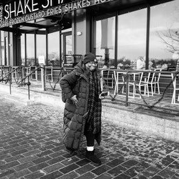 A woman walking in front of the Shake Shack at The Wharf.