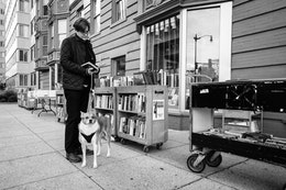 A man and his dog, looking at books at an outdoor stand near Second Story Books near Dupont Circle.