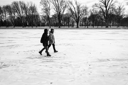 Two people walking on the frozen reflecting pool, near the Lincoln Memorial.