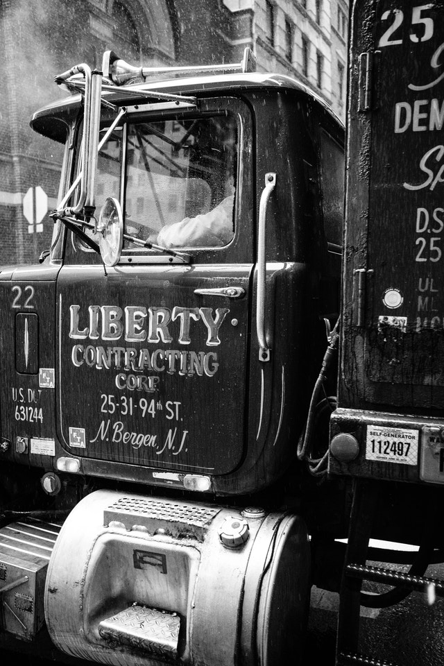 """A truck in the rain on William Street. It has """"Liberty Contracting Corp."""" written on the door in beautiful hand lettering."""