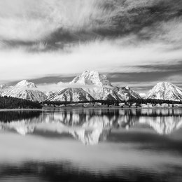 Mount Moran and other mountains in the Teton Range reflected off the surface of Jackson Lake.