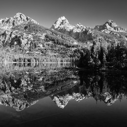 Grand Teton, Nez Perce, and other peaks in the Teton Range reflected off the waters of Taggart Lake..