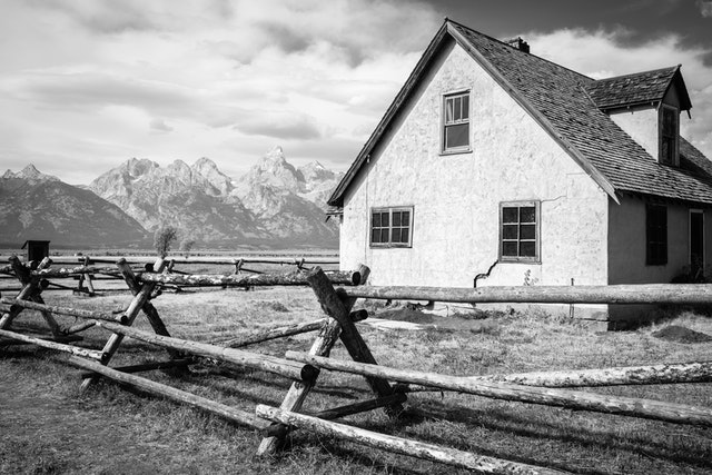 The John Moulton House, also known as the Pink House, in Mormon Row.  In the foreground, a wooden fence, and in the background, the Teton Range.
