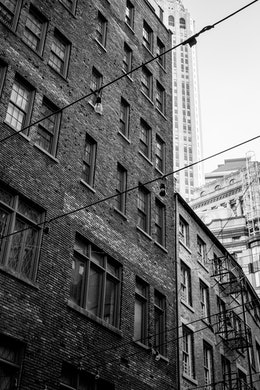 Old brick buildings and fire escapes on Stone Street in the Financial District of New York.