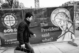 "A man walking in front of a church sign that shows Jesus facepalming and asking ""the president said what?"""