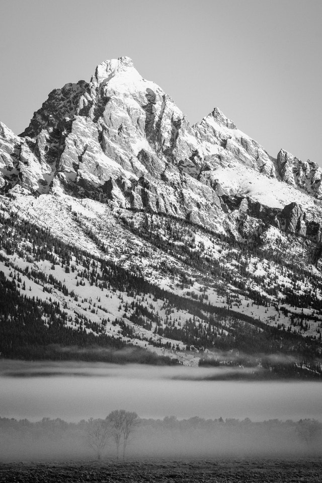 Grand Teton at sunrise, with a blanket of fog at the base of the mountain.