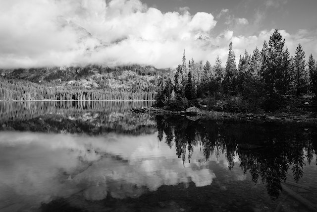Reflections on Taggart Lake. In the background, Nez Perce Peak and Teewinot Mountain shrouded in clouds.