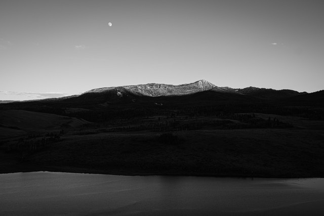 Mount Leidy at sunset, with the moon rising in the sky and the Elk Ranch Reservoir in the foreground.