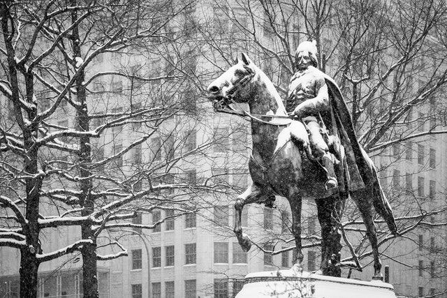 Equestrian statue of Kazimierz Pułaski at Freedom Plaza, covered in snow.