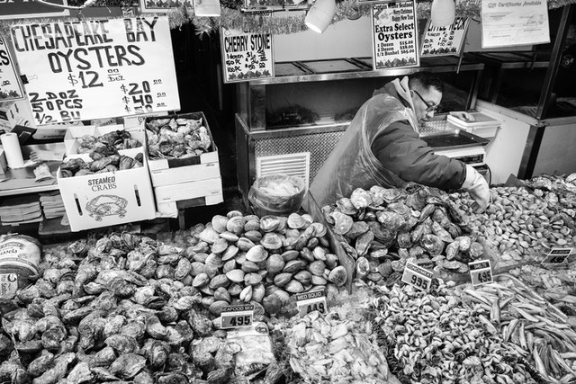 A man selling shellfish at the Maine Avenue Fish Market in Washington, DC.