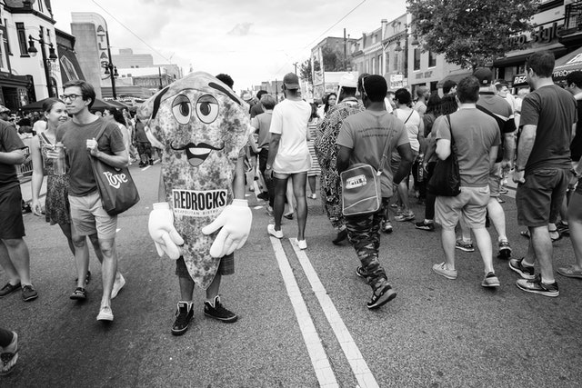 A man standing on the street in a pizza costume, at the H Street Festival in Washington, DC.