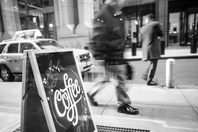 People walking by a coffee sign at the Black Fox coffee shop in New York's Financial District.