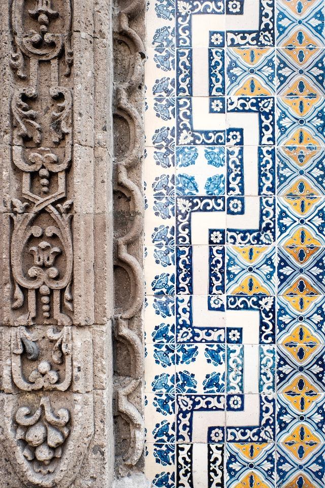 Detail of the white, yellow, and blue tiles that cover the facade of the Casa de los Azulejos in Mexico City.