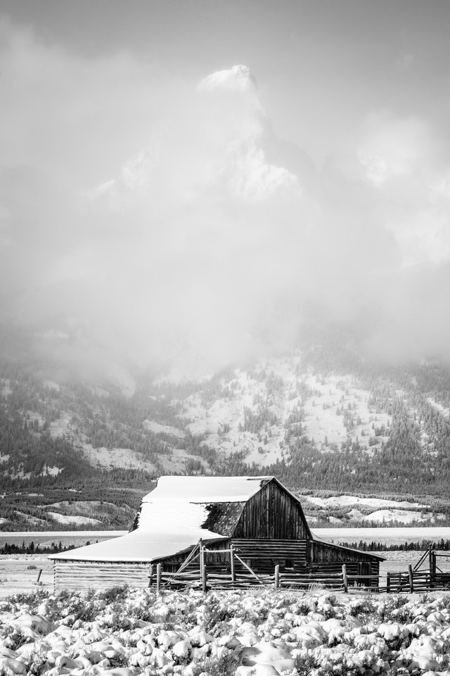 The John Moulton barn at Mormon Row, after a snowstorm. Grand Teton can be barely seen through the clouds in the background.