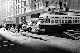 A streetcar lit by morning light on Market Street, with a pickup truck, a person on a bike, and a group of pedestrians next to it.