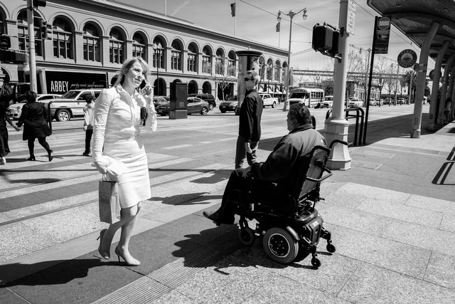 A woman dressed in white walking past a man in a wheelchair in front of the Ferry Building in San Francisco.