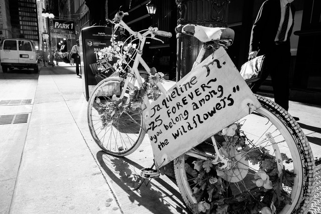 """A bicycle covered in flowers with a sign that reads """"Jaqueline M. ~25 forever~ 'you belong among the wildflowers'""""."""
