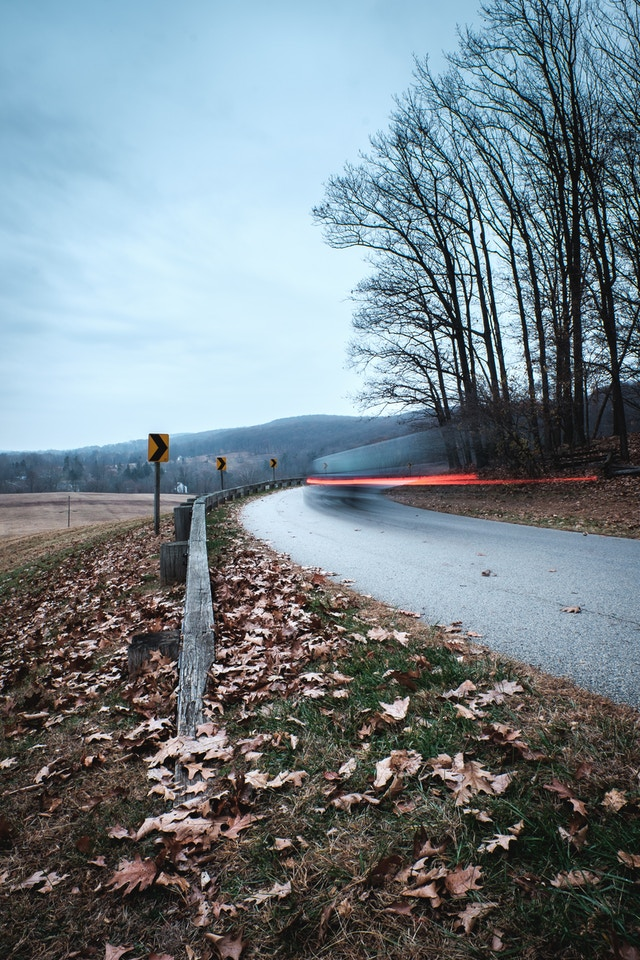 A long-exposure photo of a car driving on the road near Wayne's Woods in Valley Forge.