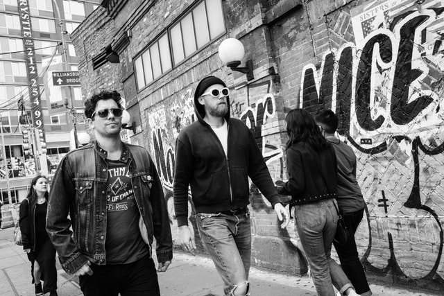 Two men wearing sunglasses and walking in front of a graffiti'd wall in Manhattan's Lower East Side.