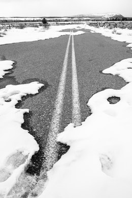 The pavement of a road partially covered in snow, leading to the Cunningham Cabin.