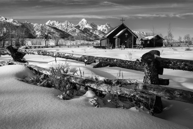 The Chapel of the Transfiguration seen behind a wooden fence in winter, with the Tetons in the background. In the foregound, sagebrush in the snow under the fence.