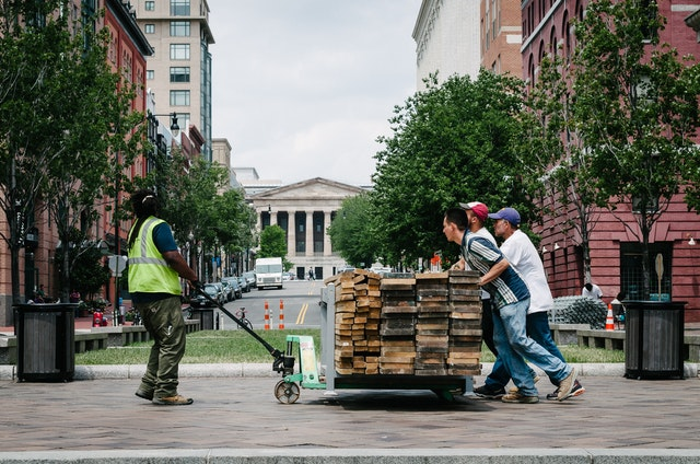 Workers pushing a cart of timber at the United States Navy Memorial in Washington, DC.