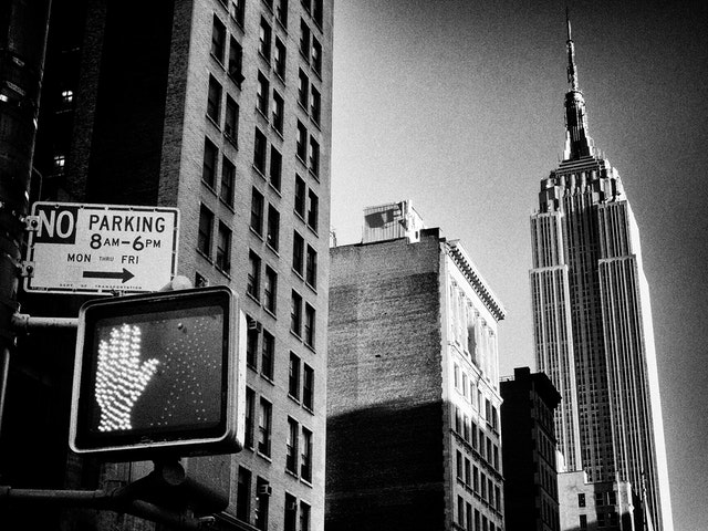 A pedestrian cross light in front of the Empire State Building.