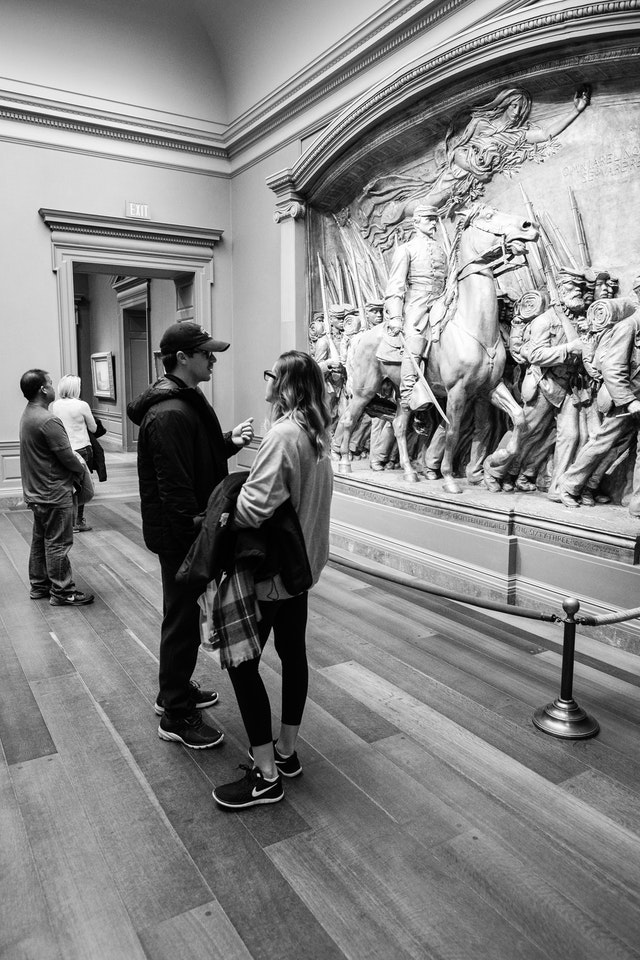 Two people talking in front of Augustus Saint-Gaudens's Shaw Memorial, at the National Gallery of Art.