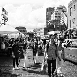 Two people holding shopping bags and walking along the street on Pike Place Market.