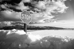 A stop sign half-buried in the snow at the Elk Ranch Flats Turnout.
