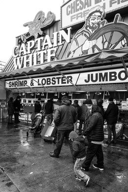 People waking in front of Captain White seafood at the Maine Avenue Fish Market.