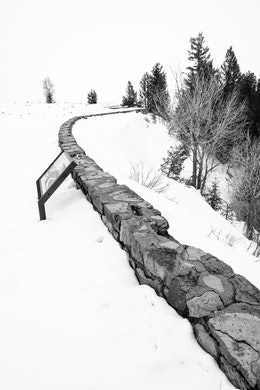 A stone wall on a very snow-covered Snake River Overlook.