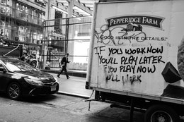 "A man walking down the street, next to a Pepperidge Farm truck graffiti'd with ""if you work now you'll play later, if you play now you'll work""."