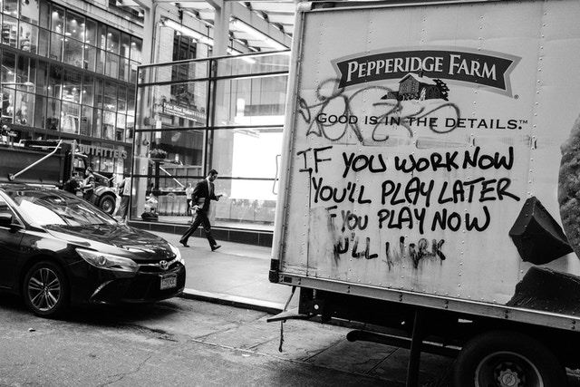 """A man walking down the street, next to a Pepperidge Farm truck graffiti'd with """"if you work now you'll play later, if you play now you'll work""""."""