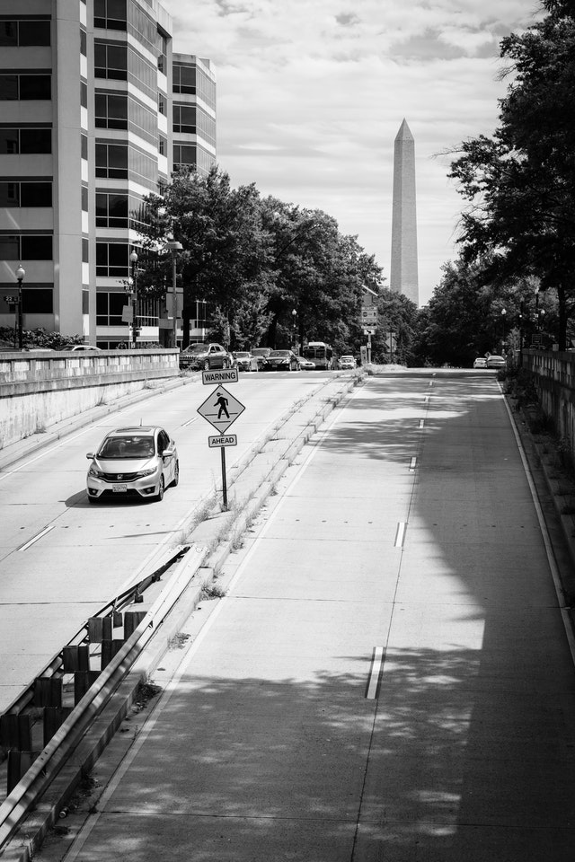 A car driving on an avenue in DC, with the Washington Monument in the background.