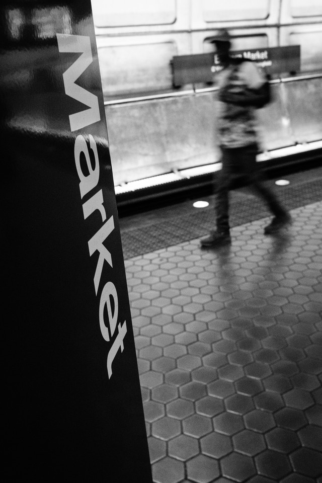 "A man walking past a sign with ""Eastern Market"" written on it on the platform at Eastern Market Metro Station in Washington, DC."