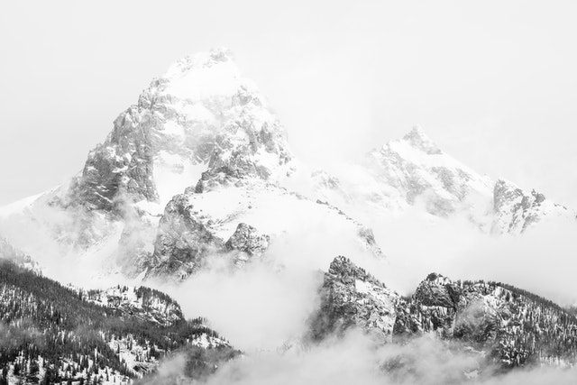 Grand Teton and Mount Owen, partially covered in clouds and fog after a storm.