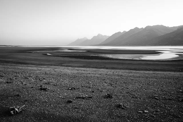 The dry lake bed of Jackson Lake after being drawn down, seen from the Jackson Lake overlook on a hazy afternoon.