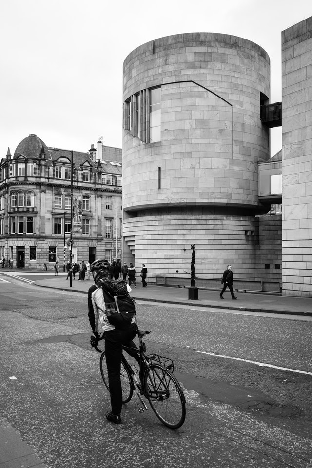 A cyclist stopped in front of the National Museum of Scotland.