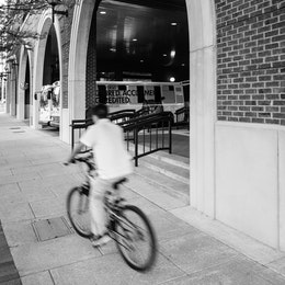A kid riding a bike past a parking garage in Chattanooga.