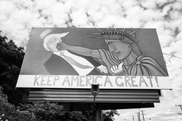 A billboard of the Statue of Liberty punching Donald Trump in the mouth.