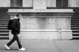 A man walking in front of the statue of George Washington at New York's Federal Hall.