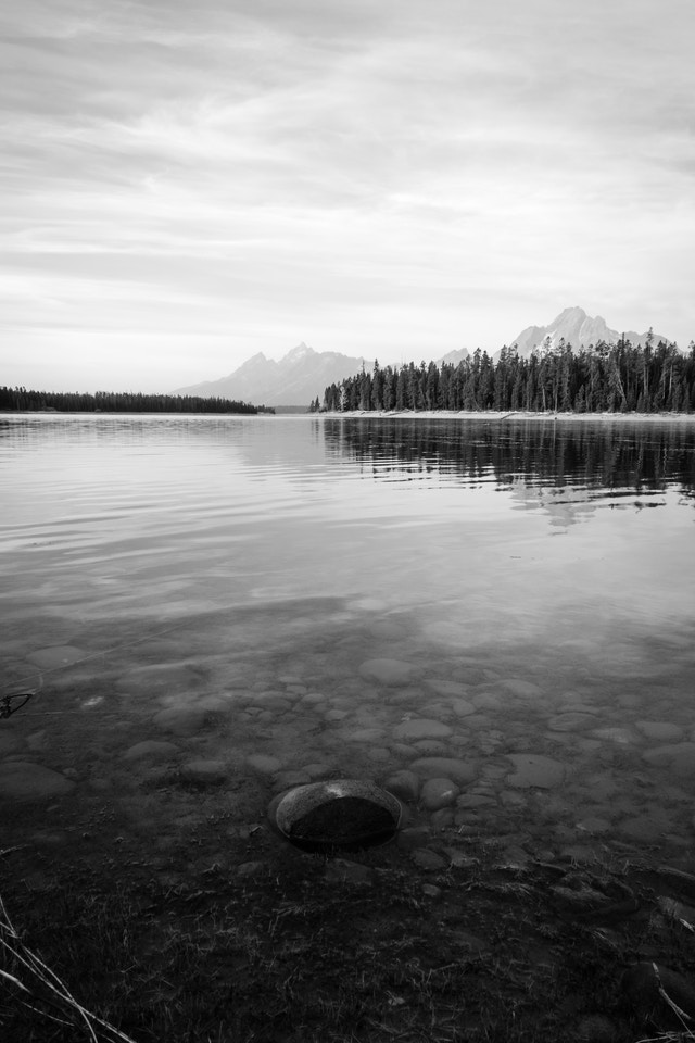A rock on the shore of Jackson Lake at Grand Teton National Park, with the Tetons and Mt. Moran in the background.