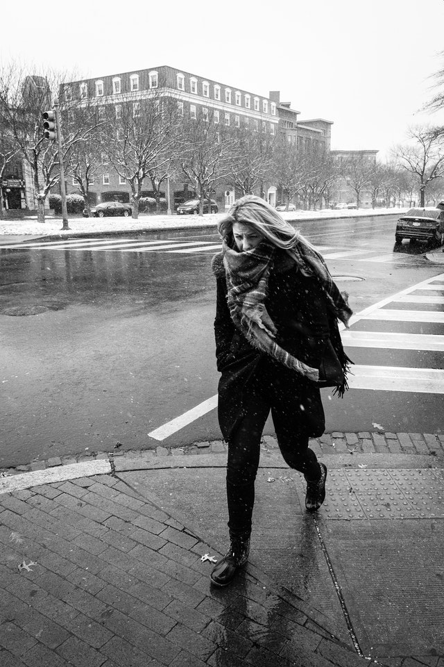 A woman grimaces while crossing the street in the snow, in Capitol Hill.
