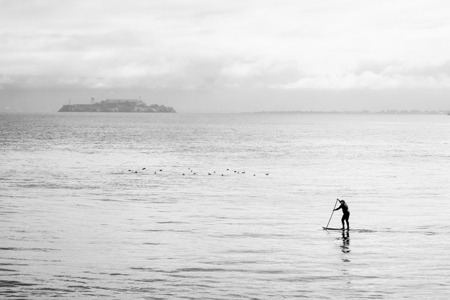One of the many surfers at Fort Point, under the Golden Gate bridge, with Alcatraz Island in the background.