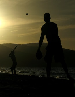 Silhouette photo of a man playing baseball with a boy at sunset on the beach in Cumaná, Venezuela.