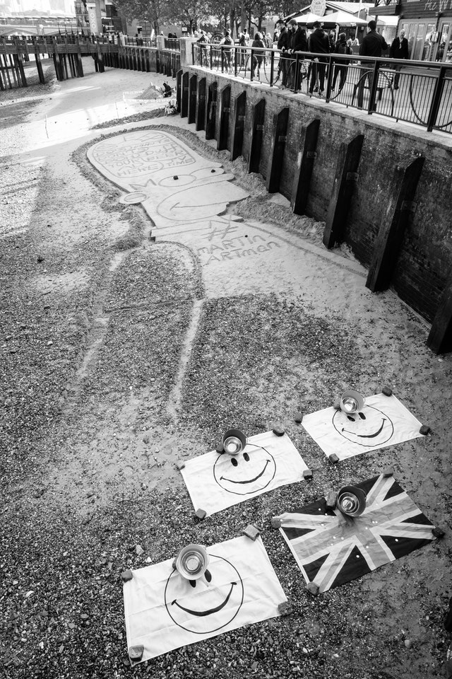A drawing of Homer Simpson on the sand on the bank of the river Thames.